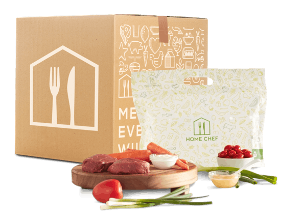 Green onions, sweet potatoes, tomatoes, and carrots sit on a cutting board, ready to be chopped up for dinner. A Home Chef meal bag and delivery box sit behind them, featuring a simple pattern of the same objects printed on their sides.